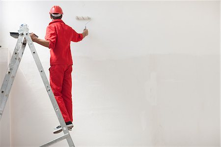 Decorator on step ladder painting white wall Stock Photo - Premium Royalty-Free, Code: 614-06814024
