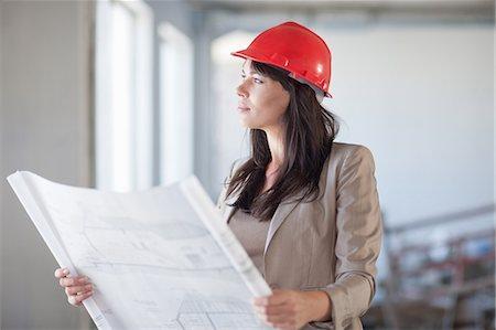 Female architect holding blueprint Stock Photo - Premium Royalty-Free, Code: 614-06814027