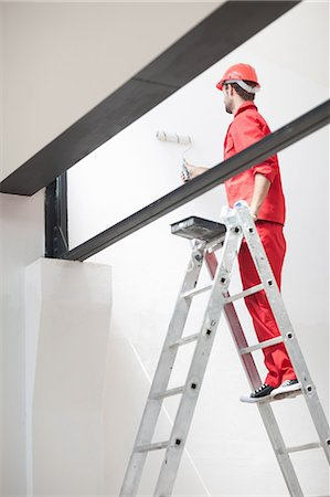 painting - Decorator on ladder painting interior wall Stock Photo - Premium Royalty-Free, Code: 614-06814022