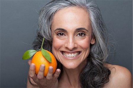Mature woman holding orange Stock Photo - Premium Royalty-Free, Code: 614-06814174