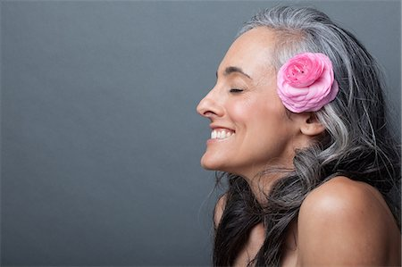 Mature woman with pink flower in hair, eyes closed Stock Photo - Premium Royalty-Free, Code: 614-06814175