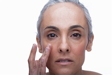 Mature woman touching face Stock Photo - Premium Royalty-Free, Code: 614-06814177