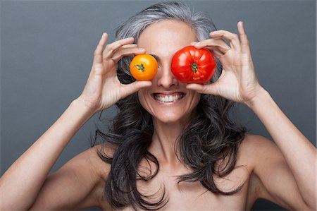 Mature woman covering eyes with red and yellow tomato Stock Photo - Premium Royalty-Free, Code: 614-06814171
