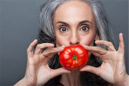 Mature woman covering mouth with red tomato Stock Photo - Premium Royalty-Free, Code: 614-06814172