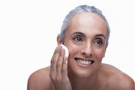 Mature woman cleansing face Stock Photo - Premium Royalty-Free, Code: 614-06814180