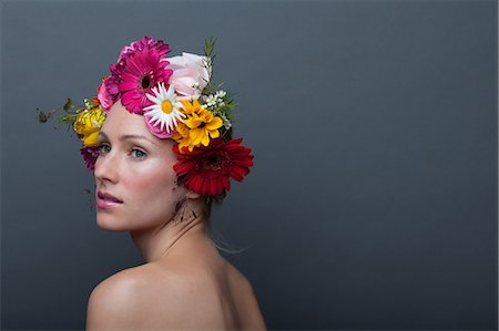 Young woman wearing garland of flowers on head Stock Photo - Premium Royalty-Free, Code: 614-06814183