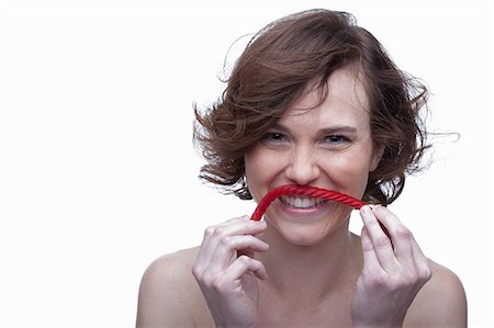 short hair - Young woman holding candy underneath nose Stock Photo - Premium Royalty-Free, Code: 614-06814217