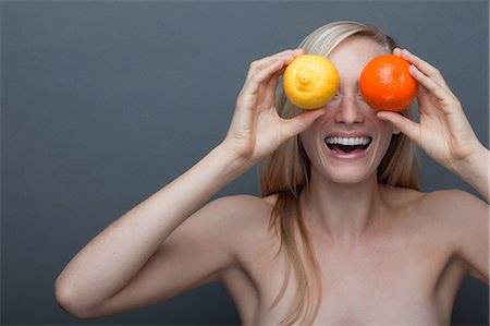Young woman covering eyes with orange and lemon Stock Photo - Premium Royalty-Free, Code: 614-06814242