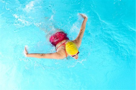 Mature woman doing butterfly stroke in swimming pool Stock Photo - Premium Royalty-Free, Code: 614-06814263