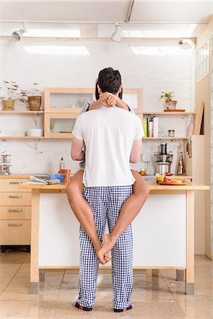 Young couple embracing in kitchen Stock Photo - Premium Royalty-Free, Code: 614-06814317
