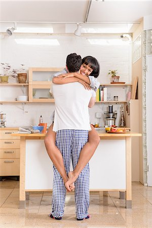 Young couple embracing in kitchen Stock Photo - Premium Royalty-Free, Code: 614-06814318