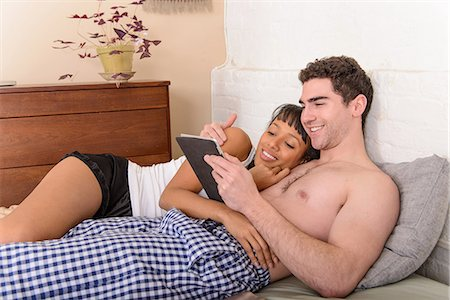 Young couple watching digital tablet in bed Stock Photo - Premium Royalty-Free, Code: 614-06814335