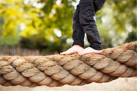 Male toddler crossing rope bridge Stock Photo - Premium Royalty-Free, Code: 614-06814359
