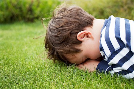 Male toddler hiding face down on grass Stock Photo - Premium Royalty-Free, Code: 614-06814367
