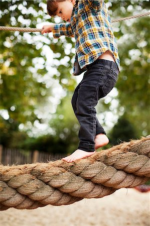 Male toddler crossing rope bridge Stock Photo - Premium Royalty-Free, Code: 614-06814360