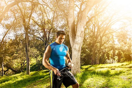 Young man exercising in forest holding earphones Stock Photo - Premium Royalty-Free, Code: 614-06813171