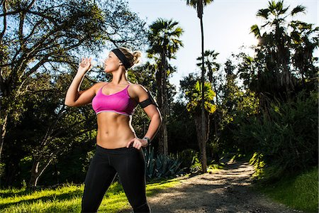 Young woman exercising in forest drinking mineral water Stock Photo - Premium Royalty-Free, Code: 614-06813189