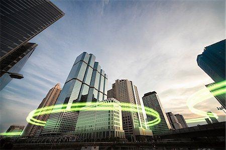 futuristic - Green light trails surrounding skyscrapers Stock Photo - Premium Royalty-Free, Code: 614-06813408