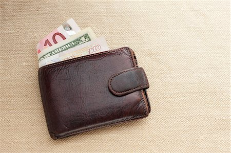 Brown leather wallet with various currencies Stock Photo - Premium Royalty-Free, Code: 614-06813517