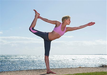 stretch - Young woman doing yoga by sea Stock Photo - Premium Royalty-Free, Code: 614-06813535