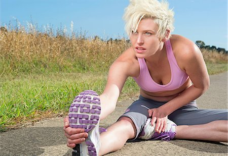 Young woman stretching hamstrings Stock Photo - Premium Royalty-Free, Code: 614-06813540