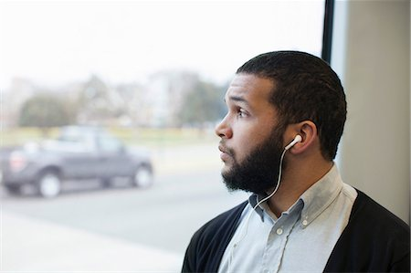 Young man traveling on light train wearing earphones Stock Photo - Premium Royalty-Free, Code: 614-06813573