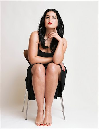 fat lady sitting - Young woman sitting on chair Stock Photo - Premium Royalty-Free, Code: 614-06813583