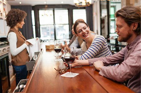Woman and man at bar chatting and checking cell phone Fotografie stock - Premium Royalty-Free, Codice: 614-06813624