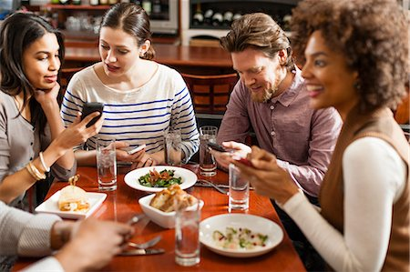 restaurant - Friends at restaurant texting and showing photos using cell phones Stock Photo - Premium Royalty-Free, Code: 614-06813687