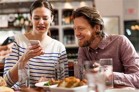 showing - Friends at restaurant texting and showing photos using cell phones Stock Photo - Premium Royalty-Free, Code: 614-06813689