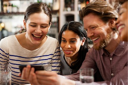 showing - Friends at restaurant texting and showing photos using cell phones Stock Photo - Premium Royalty-Free, Code: 614-06813692