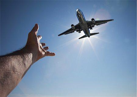 Hand reaching for aeroplane in sky Stock Photo - Premium Royalty-Free, Code: 614-06813703