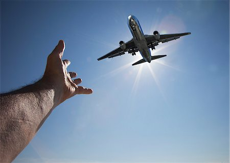 Hand reaching for aeroplane in sky Stock Photo - Premium Royalty-Free, Code: 614-06813703