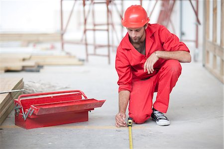 Builder with tool box and pencil measuring floor on construction site Stock Photo - Premium Royalty-Free, Code: 614-06813856
