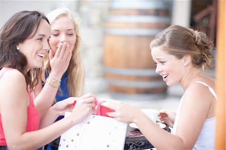 Young women showing each other their shopping Stock Photo - Premium Royalty-Free, Code: 614-06813892