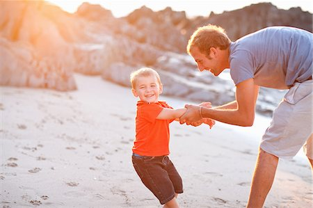Father playing with son on beach Stock Photo - Premium Royalty-Free, Code: 614-06813926