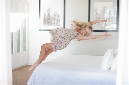 Young woman jumping on bed Stock Photo - Premium Royalty-Free, Code: 614-06813941
