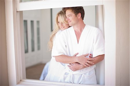 Young couple wearing bathrobes by window Stock Photo - Premium Royalty-Free, Code: 614-06813955
