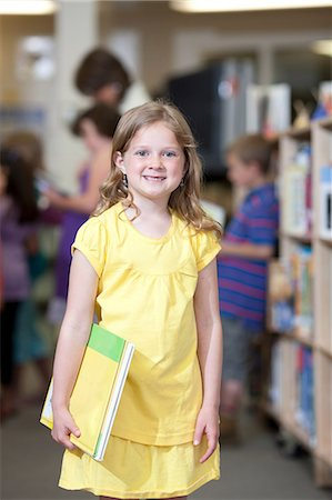 Schoolgirl holding book in library and smiling, portrait Stock Photo - Premium Royalty-Free, Code: 614-06895765