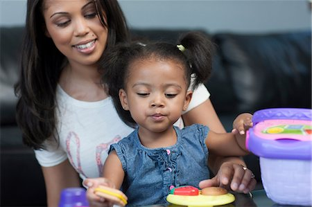 Mid adult woman watching daughter play with toys, smiling Stock Photo - Premium Royalty-Free, Code: 614-06895936
