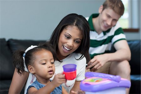 Mid adult woman watching daughter play with toys, smiling Stock Photo - Premium Royalty-Free, Code: 614-06895937