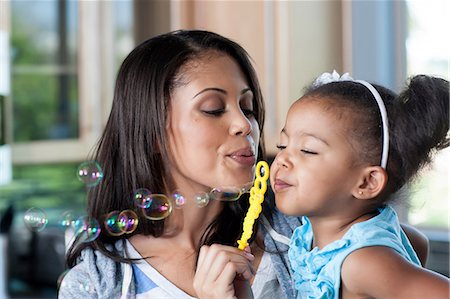 Mid adult mother and young girl blowing bubbles, close up Stock Photo - Premium Royalty-Free, Code: 614-06895950