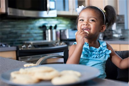 self indulgence - Young girl eating biscuits Stock Photo - Premium Royalty-Free, Code: 614-06895951