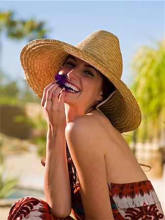 Young woman wearing sun hat and holding purple flower petal, portrait Stock Photo - Premium Royalty-Free, Code: 614-06895985