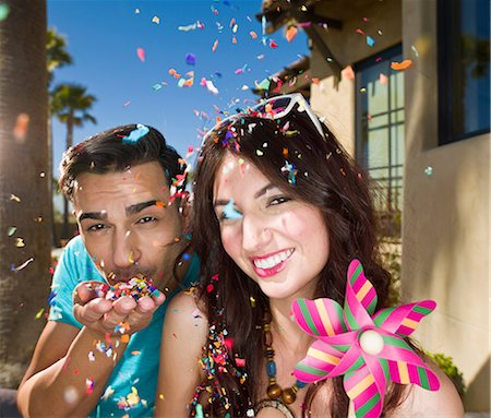 Young couple blowing confetti and smiling, portrait Stock Photo - Premium Royalty-Free, Code: 614-06895988