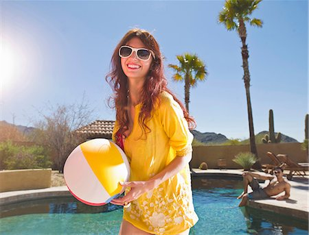 Young woman holding beach ball at poolside, portrait Stock Photo - Premium Royalty-Free, Code: 614-06895994
