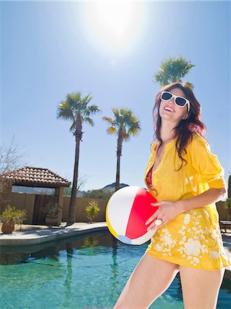Young woman holding beach ball at poolside, portrait Stock Photo - Premium Royalty-Free, Code: 614-06895995