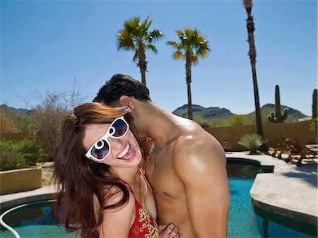 Young couple embracing at poolside, smiling Stock Photo - Premium Royalty-Free, Code: 614-06895998