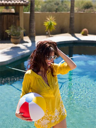 funky - Young woman holding beach ball at poolside, smiling Stock Photo - Premium Royalty-Free, Code: 614-06895993