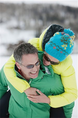 Mature man carrying young woman on back in snow, laughing Stock Photo - Premium Royalty-Free, Code: 614-06896077